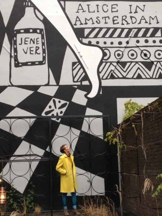 Alice in a yellow wool coat in the Alice in Wonderland inspired garden at the Andaz Hotel Amsterdam